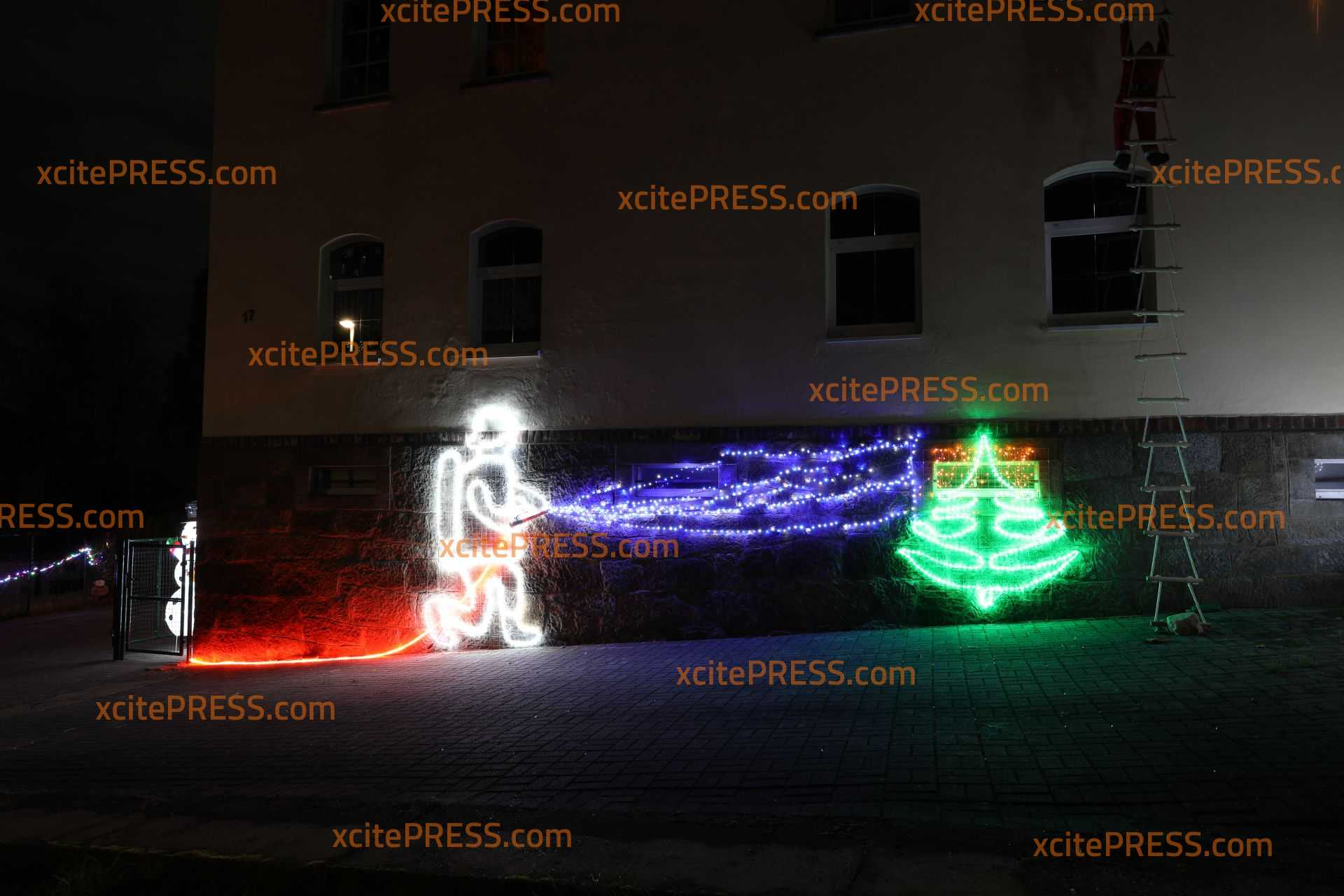 Kreative Weihnachtsdekoration aus Lichterschläuchen: Feuerwehrmann löscht brennenden Weihnachtsbaum